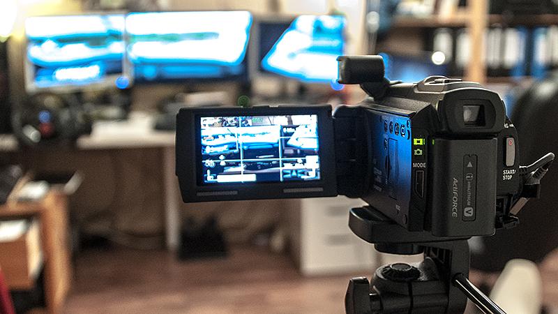 Foto hinter der Kamera mit Blick auf die drei Monitore